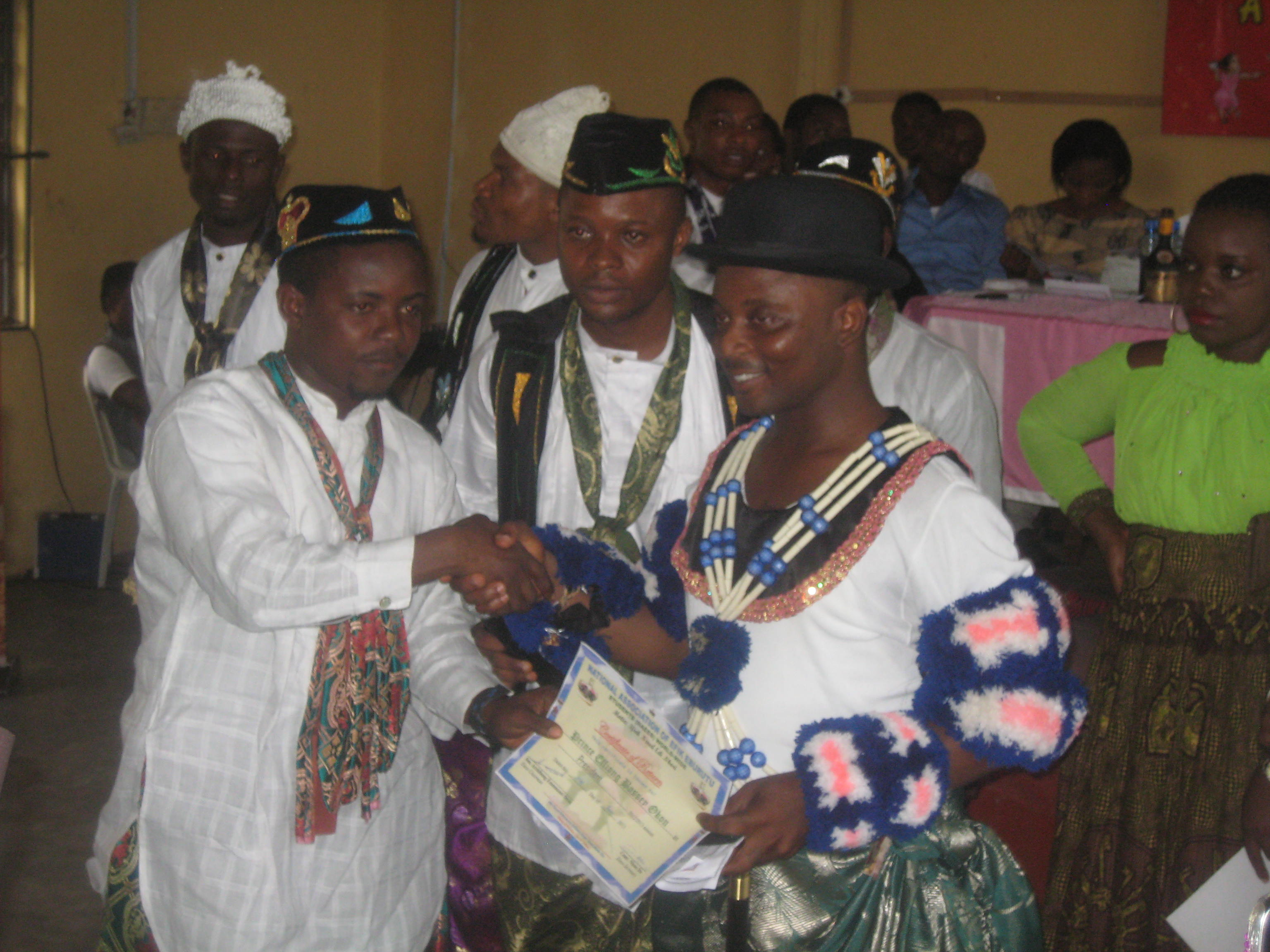 The outgoing president of the Efik Students Union presenting a certificate to the new president