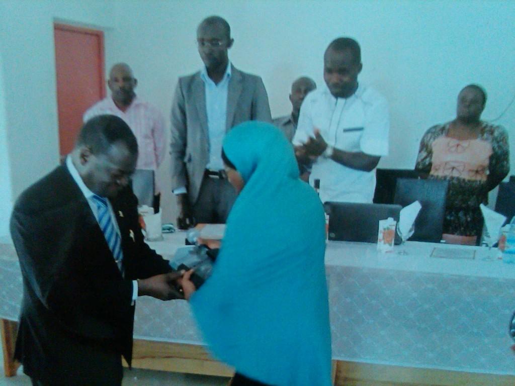 Dr. Ibili receiving the award from Comrade Bilkis