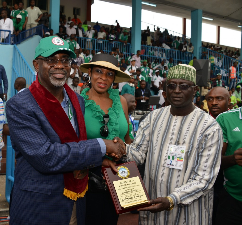 Cross River State Governor, Senator Liyel Imoke (L) receiving a plaque from the President Sports Writers Association of Nigeria (SWAN), Mallam Saidu Abubarka while his wife Mrs. Obioma Liyel Imoke(M) watches shortly after  his investiture as the Patron of the Association at half time during the match between Nigeria and Ethiopia in Calabar on Saturday