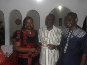 Obudu Council Boss, Hon Emmanuel Ugbe in the middle displaying the award. To his left is Kakum Development Association Calabar Branch Chairman and to his left is the Chairman's wife