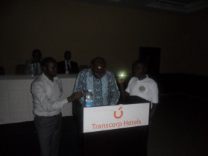 Mr. Kanu Agabi, SAN reading with the aid of a touch light because in the course of speaking electricity supply went off