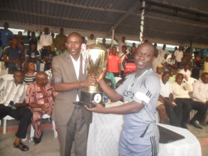 The representative of the Commissioner of Sports presenting the trophy to the captain of Team Customs, winners of the maiden edition of the Cross River State Security Unity Cup