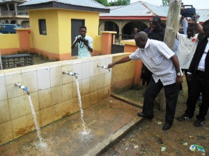 Senate Leader, Victor Ndoma Egba, SAN opening a tap faucet during the project inspection tour at Mkpani, Yakurr LGA