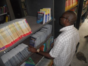 Senator Ndoma Egba, inspecting books in a library facilitated oing through books