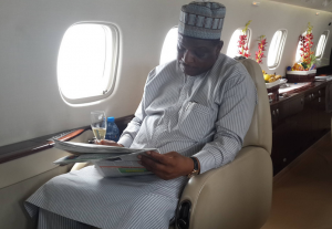 Mr. Jedy Agba reading about Cross River in a local newspaper aboard the chartered jet