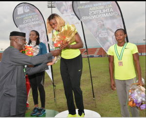 Cross River State Governor, Senator Liyel Imoke decorating  Blessing Okagbare with the Gold medal/ bouquet of flower as she emerged champion in the women's 100mtrs  finals finishing at 11.06  during the ongoing Cross River/All Nigerian Athletics Championship 2014..Finishing in second place with 11.17 2nd is Gloria Asumnu also of Delta state and in 3rd place is Sule Justina 11.65 seconds in Calabar
