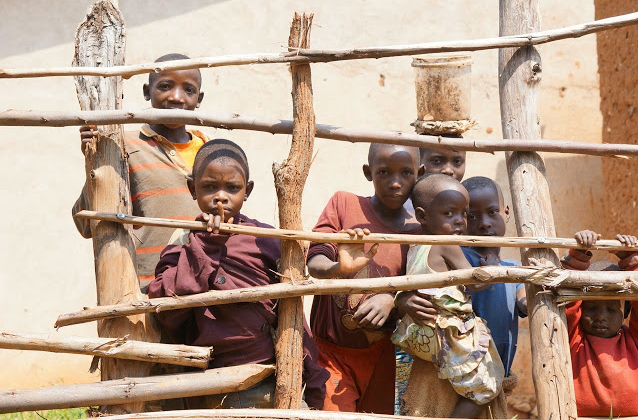 Bakassi children beholding their fate through a wooden fence