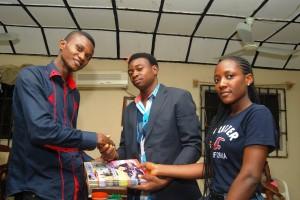 Akpet Obaji, presenting copies of CrossRiverWatch to Inno Frank Akpeke, MD/CEO, Mountain Cinema Nigeria