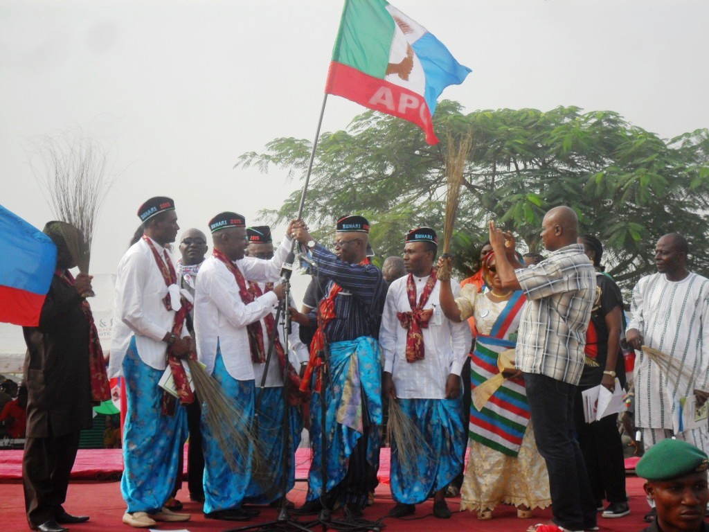 Odey Ochicha receiving the party flag from the APC National Chairman