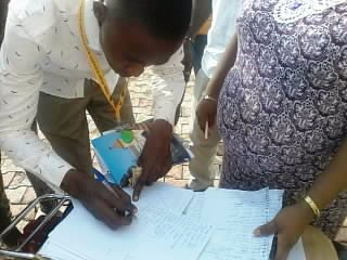 An-Applicant-holding-his-two-hundred-Naira-while-writing-his-name-on-the-collection-sheet