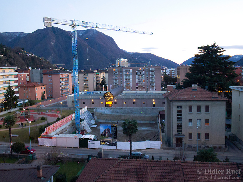 Switzerland. Canton Ticino. Lugano. Construction site for a new house with flats for sale. A supermarket Coop with lights on. Sunset and twilight. 3.02.13 © 2013 Didier Ruef