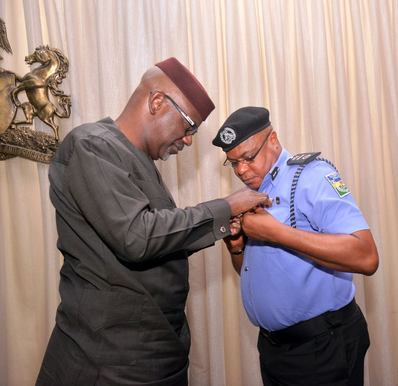 Governor Imoke decorating the AIG Zone 6, Mr. Tunde Ogunsakin when the latter paid him a courtesy visit in his office in Calabar