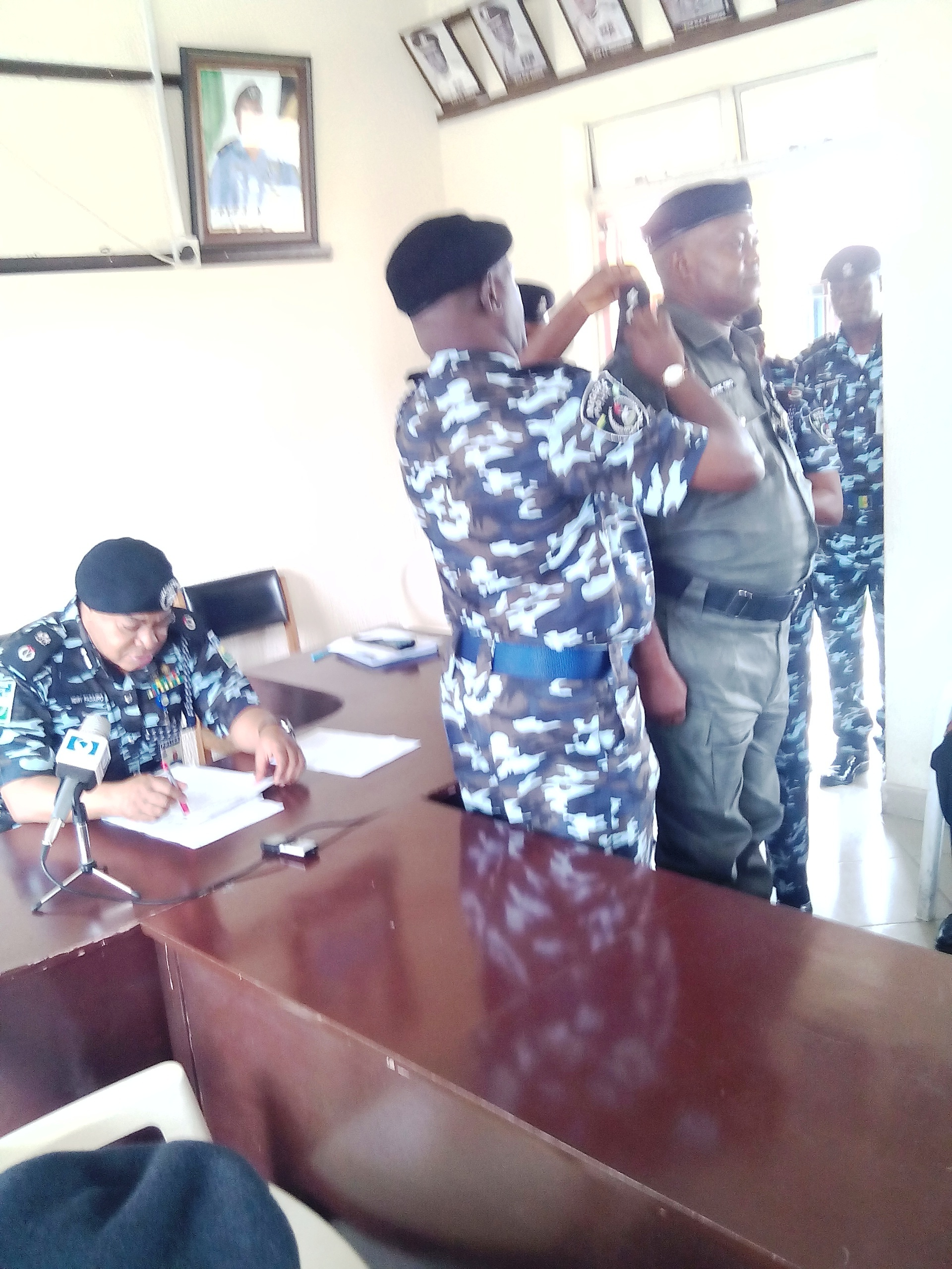 The Commissioner (left) addressing the participants while a senior officer decorates one of the promoted officer