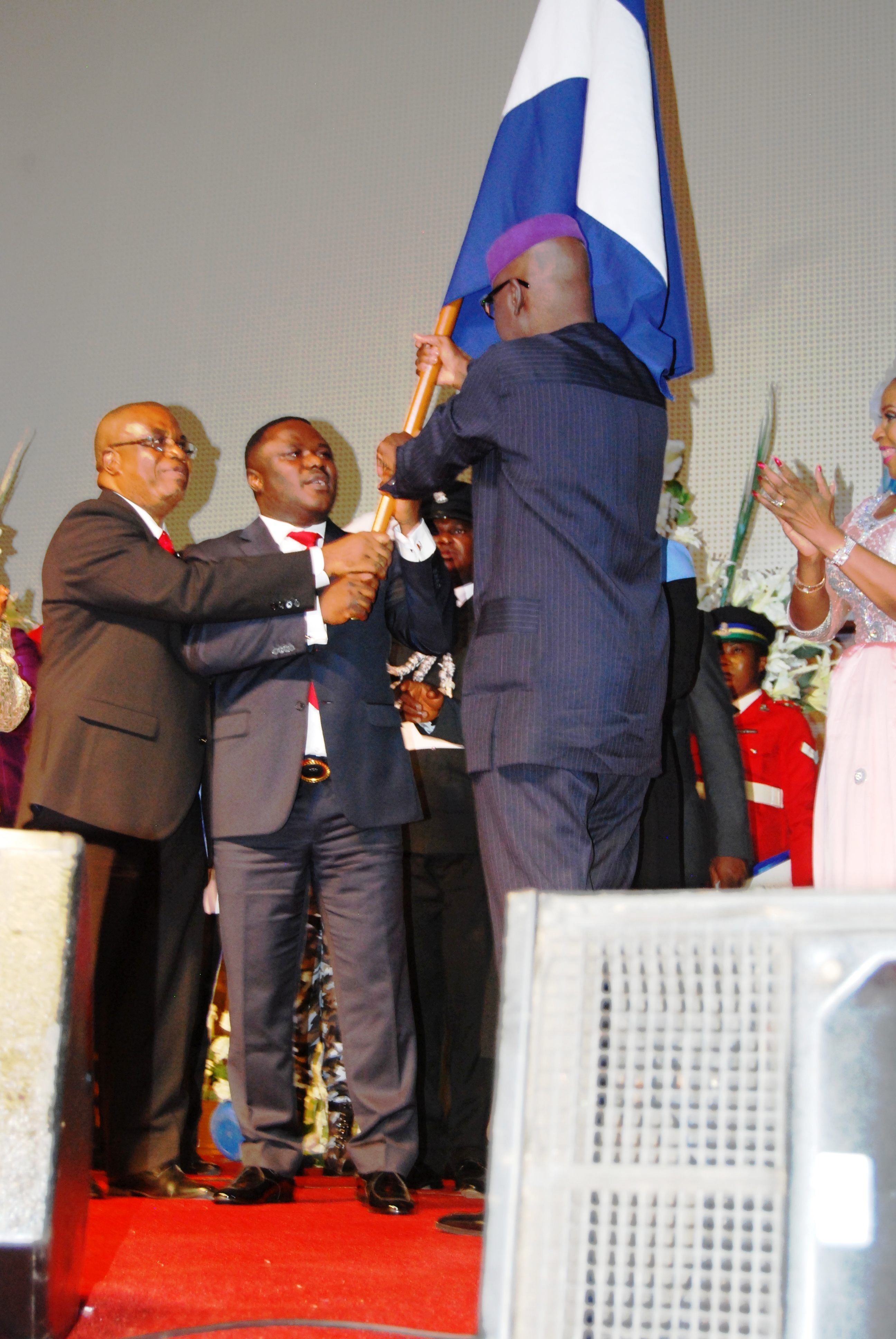 The former governor, Senator Liyel Imoke handing over the state flag to his successor, Senator (Prof) Ben Ayade aided by his deputy, Prof. Evara Esu