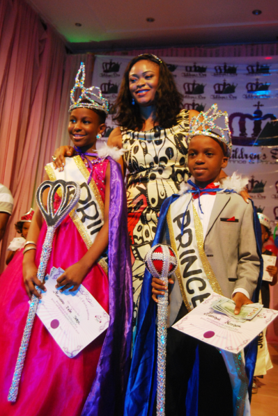 The new Prince and Princess bearing their certificates and prize money and the event organizer in the middle