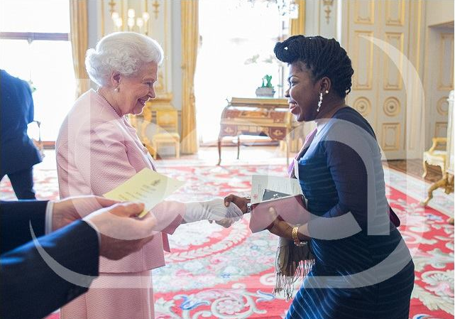 Esther Eshiet in a royal handshake with Queen Elizabeth II at Buckingham Palace, UK