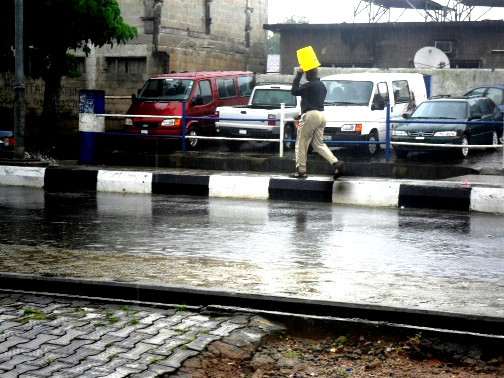 Plastic bucket to the rescue in the absence of umbrella: It's raining season guys. Location: Marian road Calabar, over the weekend