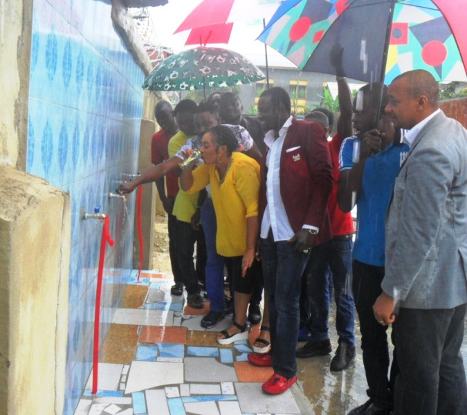Engineer Moses Akpoba aiding his wife to taste the water after cutting the ribbon while others watch