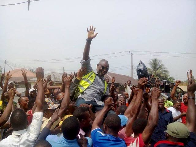 The workers lifting up the DG after he promised them payment on Wednesday