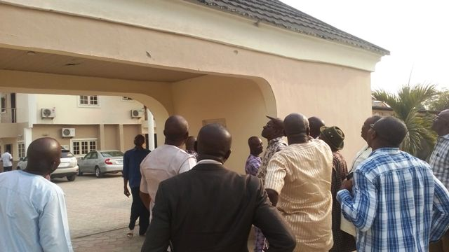 hon paul adah pointing to the bullet spots on the wall of the entrance to his house while other APC members watch