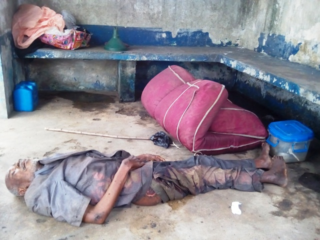 Lifeless body of the unidentified homeless man and his luggage presently lying at SPC bus stop, by Highway Calabar
