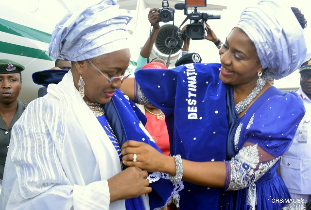 Wife of the President, Aisha Buhari (L) being decorated on arrival in Calabar by the Wife of the Cross River State Governor, Linda Ayade