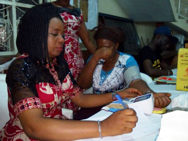 Health Commissioner Inyang Asibong testing beneficiaries for high blood pressure