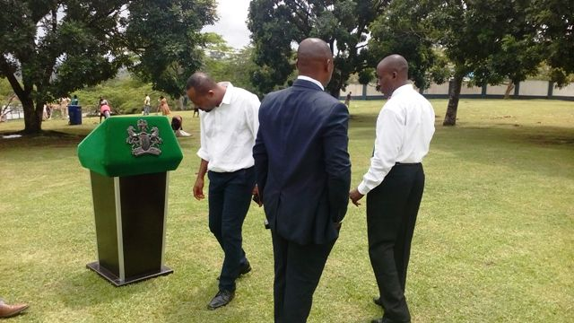 The governor's security details setting up a podium and carrying out security sweeping before the press briefing