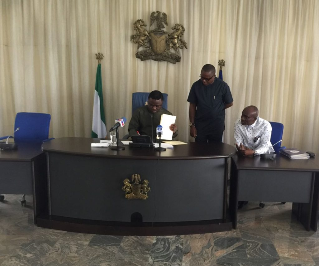 Governor Ayade (sitting left) signing the bills while the speaker (sitting) and the State Chief of Protocol watch