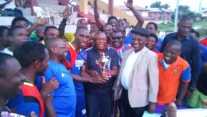 The State Nigeria Medical Association Chairman and the team captain holding the trophy amidst celebration.