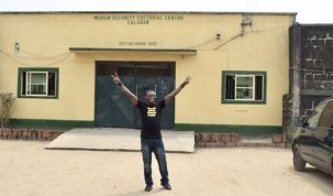 IN THIS PHOTO: CrossRiverWatch publisher and rights activist, Citizen Agba Jalingo raises both hands outside the Medium Custodial Center of the Nigerian Correctional Service in Calabar, the Cross River State capital (popularly referred to as Afokang prison) to celebrate his release after 179 days in detention following his admission to bail by Justice Sule Shuaibu of the Calabar Division of the Federal High Court. 17/2/2020. Credit: CrossRiverWatch/Oto-Obong Clement
