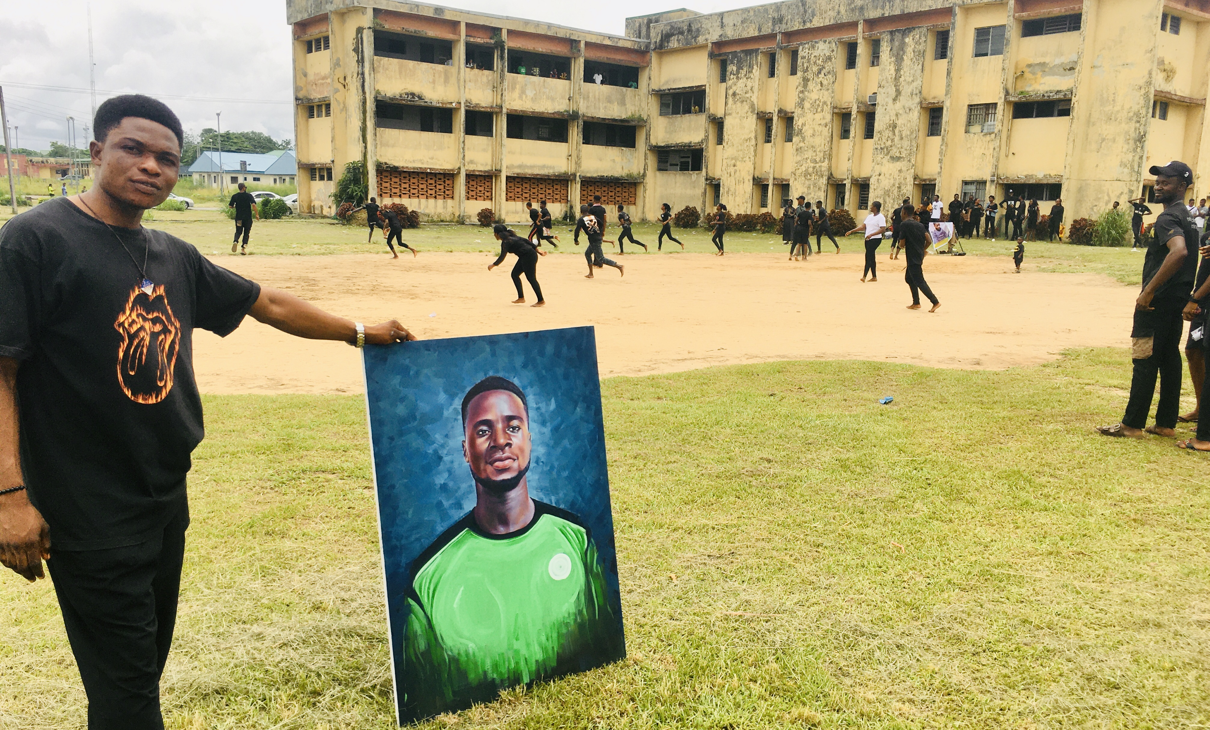 Sylvanus Okwor, Vice President of the Visual Arts and Technology Students Association holds a painted portrait of Nkasi Ford Moses while colleagues play a football game in honor of the late Ford at the Calabar campus of UNICROSS. 29/6/2021